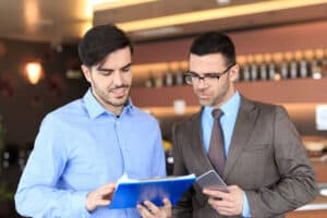 a man in a blue shirt showing another man something on a blue clipboard