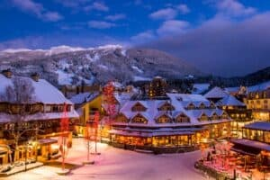 a ski resort with snow on the rooftops, outdoor lights on, snow on the ground, and ski hills in the background with mountains and pine trees