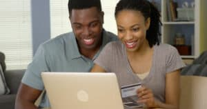 smiling young black couple using credit card to make online purchases laptop
