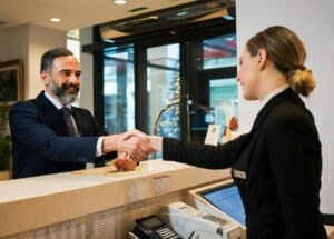 a man in a suit and graying beard shaking hands with a female concierge from behind a hotel desk
