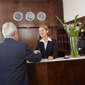 woman in a suit shaking hands with a man with grey hair across a hotel front desk