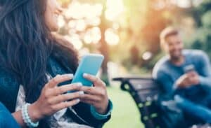 close up of a woman holding a smart phone while sitting on a park bench and a man using a smartphone in the background