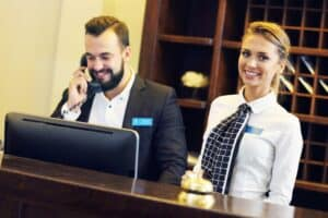 a man in a suit on the phone and a woman next to him smiling, both behind a hotel front desk