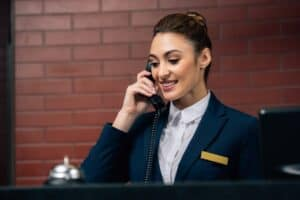 woman wearing a navy suit talking on the phone behind a hotel concierge desk with a brick wall in the back