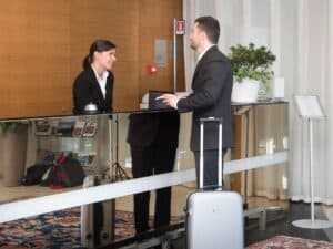 a man with a small grey suitcase at a hotel concierge desk talking to a woman behind the desk