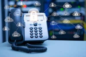 an icon of a lock in a cloud with a web of telecommunication icons branching outwards with a landline in the background