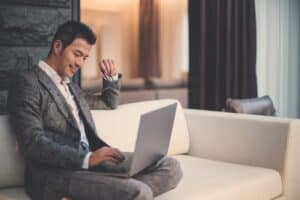 man in a gray suit sitting on a white couch looking at a computer while in a hotel