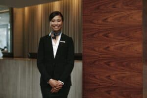 woman wearing a black suit, smiling and facing the camera in front of a hotel concierge desk and wood wall
