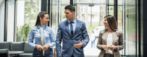 three employees walking together, looking at each other, and wearing business professional clothing