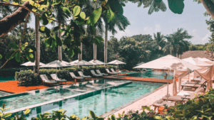 turquoise tiled outdoor pool with white cushioned lounge chairs and umbrellas lining the pool. Tall trees surrounding the pool area and brown wood decks