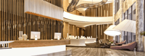 two story hotel lobby with large lighting, a stone wall, front desk with wood accents and two computer monitors, and a large hanging ceiling decoration. tones of brown, yellow, white, grey and gold