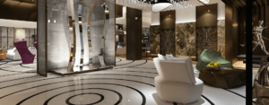 hotel lobby with a white floor that has a circular design, futuristic looking chairs, tabes, and sculpture. Large stone accent wall and crystal installation on the ceiling, whites, greys, brown accents