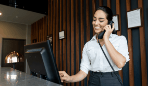 A woman behind a hotel desk wearing a white top, dark grey pants, smiling while on the phone and touching a computer monitor